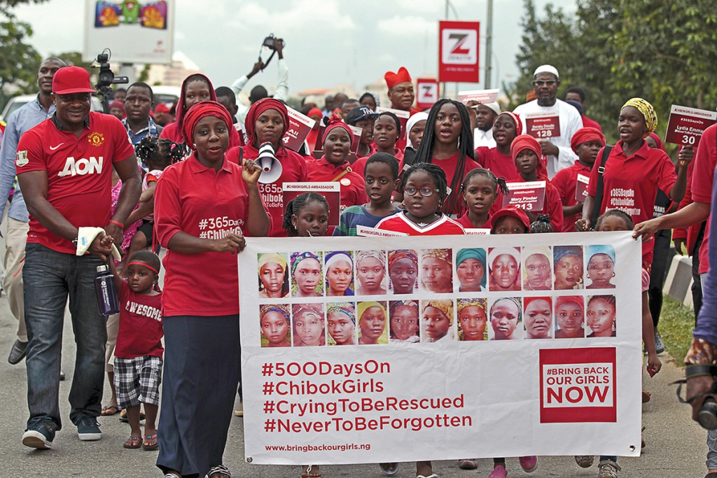 Bring Back Our Girls (BBOG) campaigners take part in a protest procession marking the 500th day since the abduction of girls in Chibok, along a road in Abuja