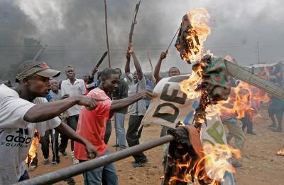 Opposition supporters burn banner